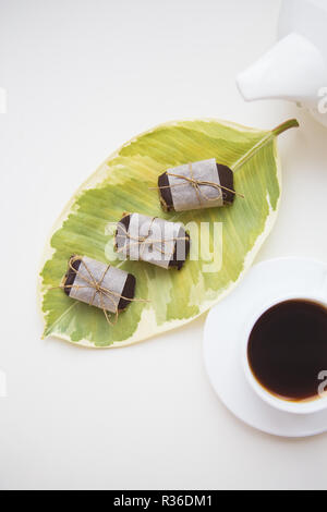 Two cups of coffee with a teapot stand on a table, candy made from nuts. - Stock Photo