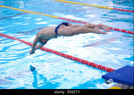 Male swimmer in bathing suit jumping into water of a swimming pool. Kiev, Ukraine. October 25, 2018 - Stock Photo