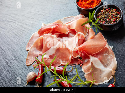 spanish dry-cured ham, jamon curado thinly sliced and served on a black stone plate with rosemary and species, horizontal view from above, close-up - Stock Photo