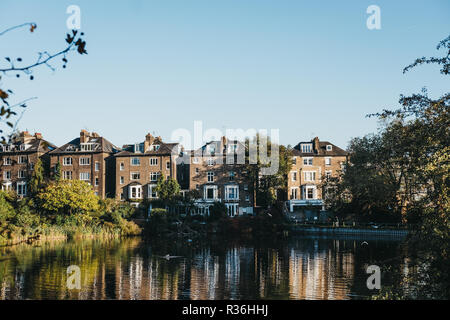 London, UK - October 27, 2018: Row of semi-detached houses in Hampstead, facing a pond in Hampstead Heath. Hampstead Heath covers 320 hectares one of  - Stock Photo
