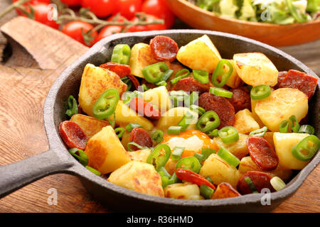 Baked potatoes with sausage chorizo and fried egg on frying pan - Stock Photo