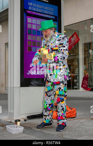 Bearded busker in a jazzy suit strums for donations in Liverpool City centre high street, as Black Friday discount sales get underway. UK - Stock Photo
