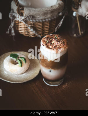 Chocolate Milk Shake with Coffee and Colorful Sugar Sprinkles As Topping and Blur doughnut and Mint Leaf on Wooden Table in Cafe - Stock Photo