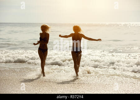 Two happy girls runs and having fun at tropical sea beach - Stock Photo