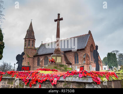 Knitted & crocheted red poppies on display together with standing soldier silhouettes, outside in UK churchyard, by war memorial. Armistice centenary. - Stock Photo