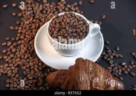 Close up of coffee cup and croissant in coffee beans on black background. - Stock Photo