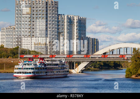 The 1978 Felix Dzerzhinsky cruise ship on the Moscow Canal in central Moscow as it approaches a railway bridge with train crossing, Russia. - Stock Photo