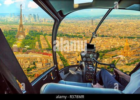 Helicopter cockpit flying on Panorama of Tour Eiffel and national residence of the Invalids in Paris, French capital, Europe. Scenic flight above Paris skyline and cityscape background. - Stock Photo