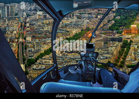 Helicopter cockpit flying on Parisian panorama aerial view of Paris skyline. Scenic flight above on Champs Elysees street and Paris skyline on sunset blue hour. - Stock Photo