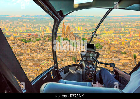 Helicopter cockpit flying on Montmartre hill skyline of Paris, French capital, Europe. Scenic flight above Sacre Coeur basilica, or sacred heart church on Montmartre hill. - Stock Photo