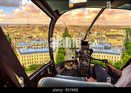Helicopter cockpit flying on Paris skyline of the French capital, Europe. Scenic flight above Place de l'Etoile and Avenue de Wagram road of Paris skyline at sunset. - Stock Photo