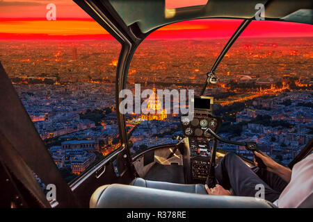 Helicopter cockpit flying aerial view of national residence of the Invalids palace at sunset in Paris, French capital, Europe. Scenic flight above Paris skyline on red sunset background. - Stock Photo