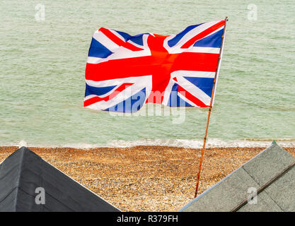 British Union Jack flag flying from a pole on beach huts at the edge of the sea on a pebble beach in Kent, England - Stock Photo