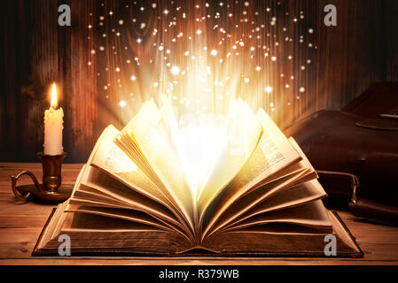 Old book with magic lights on wooden table by candlelight - Stock Photo