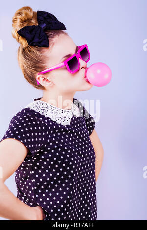 Humorous profile of a young woman making a bubble of chewing gum, hands on hips - Stock Photo