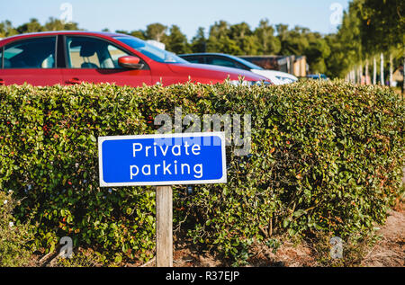 Blue colored sign PRIVATE PARKING at the entrance of car park - Stock Photo