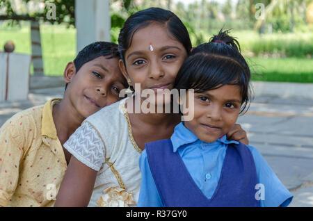 Three young Indian siblings, one boy, two girls, pose for the camera somewhere in Ranganatha, Anegundi, Karnataka, India - Stock Photo