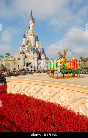 Disneyland Paris, France, November 2018: Sleeping Beauty's Castle with blue skies behind and red flowers in front - Stock Photo