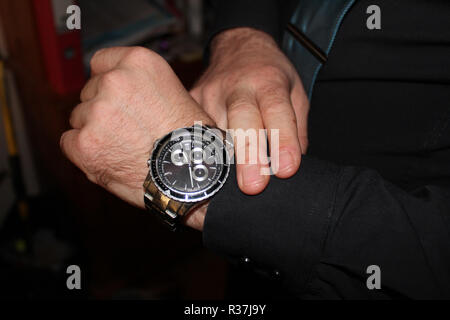 businessman in black shirt showing the time, handwatch - Stock Photo