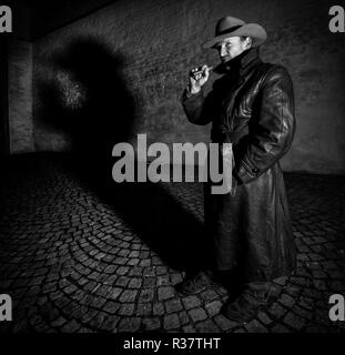 Man with hat and leather coat smokes cigar, shadow in the back, night shot, Germany
