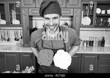 Substitute carefully. Although substitutions seem obvious they can be tricky business. Ruined dish is waste of time. Man chef substitutes broccoli with cauliflower. Chef smiling knows kitchen tricks. - Stock Photo