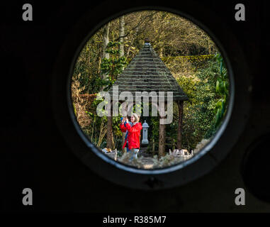 Through a port hole, a lady is seen taking a photo with her mobile phone. Taken at York Gate Garden, Adel, Leeds. - Stock Photo