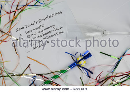 The time-honored tradition of making New Year's resolutions is depicted in this image with streamers and a champagne glass tipped over. - Stock Photo