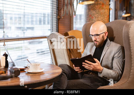 the waiter brings the electronic menu or bill in the restaurant in the form of a smartphone tablet, with built-in advertising. Successful people, businessman in comfortable cafe . - Stock Photo