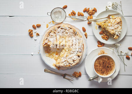 Whole delicious apple cake with almonds served on wooden table - Stock Photo