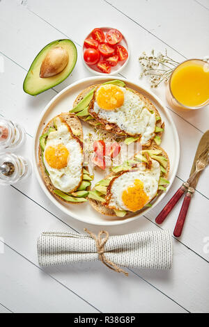 Delicious healthy breakfast with sliced avocado sandwiches with fried egg - Stock Photo