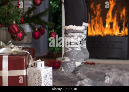 Girl feet in Christmas socket standing on fingers near fireplace and decorated Xmas tree. Christmas and New Year concept. Close up, selective focus - Stock Photo