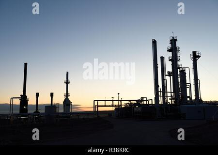 Dawn silhouette of pipes and towers at a oil and gas industry processing facility in Wyoming / USA. - Stock Photo