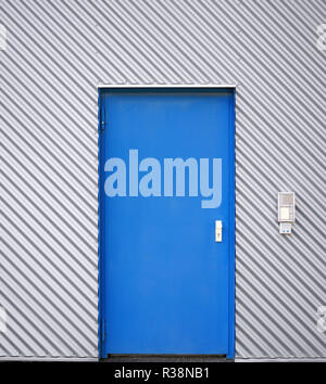 blue door in a silver corrugated metal facade - Stock Photo