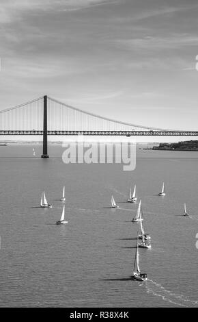 Sailboats on the Rio Tajo with Ponte 25 de Abril, monochrome, Lisbon, Portugal - Stock Photo
