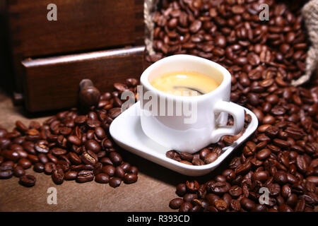 Fresh roasted coffee beans in burlap sack, coffee cup and grinder on dark background - Stock Photo