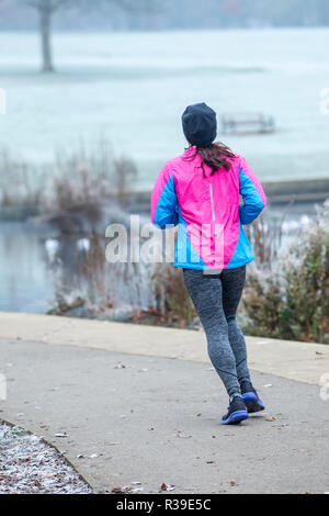 UK Weather: Northampton. 22  November 2018. A frosty start to the day in Abington Park  female jogger  enjoying the cold crisp airCredit: Keith J Smith./Alamy Live News - Stock Photo