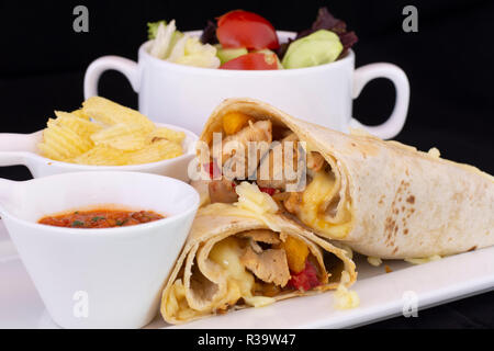 Delicious chicken wrap with salad inside with isolated black background - Stock Photo