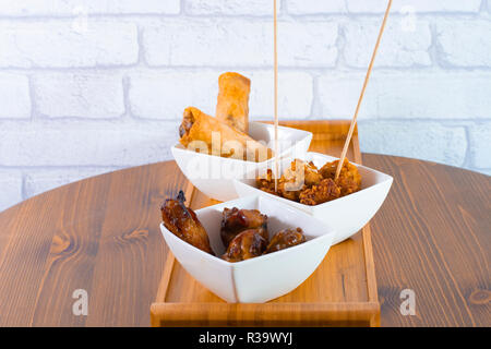 Homemade delicious spring rolls served with sweet and chilly sauces on wood table - Stock Photo