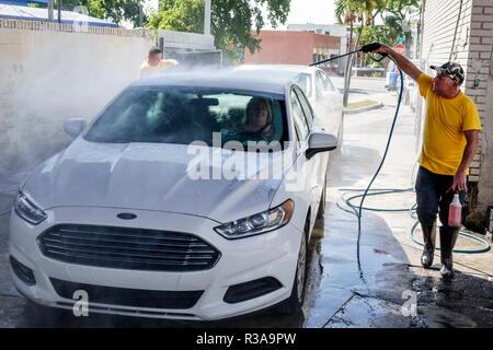 Miami Florida Little Havana car wash white Ford Fusion Hispanic man working cleaning water hose high pressure spray spraying - Stock Photo