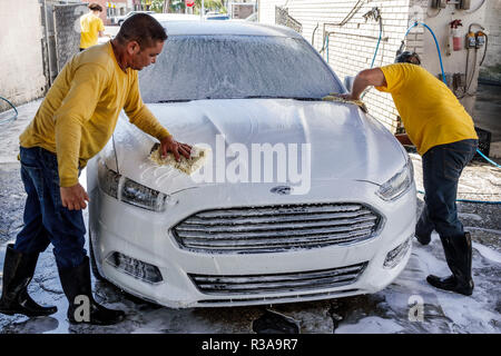 Miami Florida Little Havana car wash white Ford Fusion Hispanic man working cleaning soap soaping wiping teamwork - Stock Photo