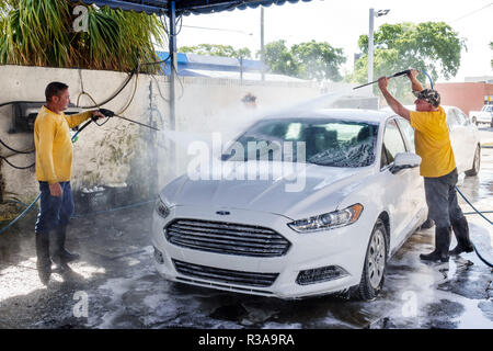 Miami Florida Little Havana car wash white Ford Fusion Hispanic man working cleaning water hose high pressure spray spraying teamwork - Stock Photo
