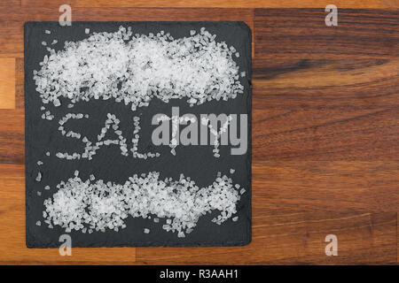 coarse salt on black slate with wooden background - Stock Photo