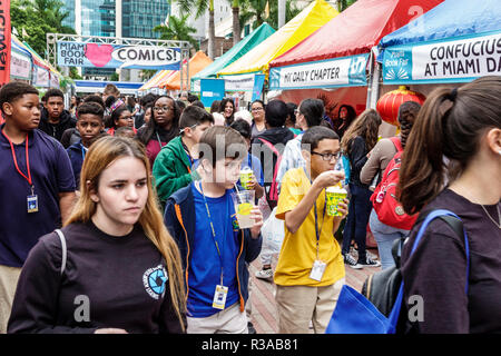 Miami Miami Florida-Dade College Book Fair annual event booths stalls vendors booksellers books sale shopping student boy girl Hispanic Black friends - Stock Photo