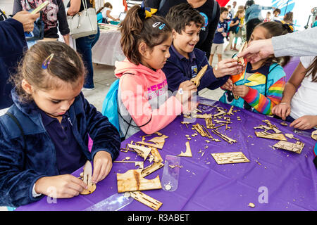 Miami Miami Florida-Dade College Book Fair annual event arts & crafts tent student boy girl Hispanic making - Stock Photo