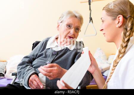 nurse cares for senior in altenheim - Stock Photo