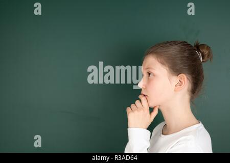 student at blackboard while thinking - Stock Photo
