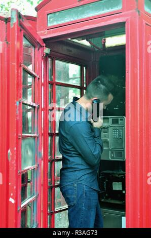 London, England, United Kingdom. Man using a traditional red telephone box along Park Lane on the edge of Hyde Park in London's West End. - Stock Photo
