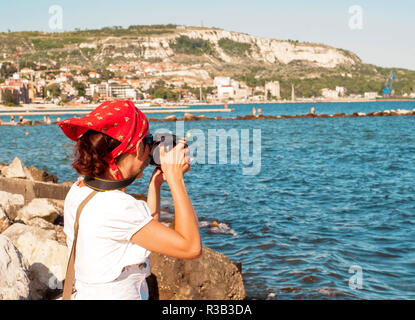 Pretty young girl takes pictures at the seaside - Stock Photo