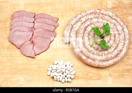 Spiral shaped sausages, beef meat slices, beans and parsley leaves on wooden board - Stock Photo
