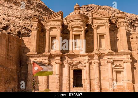 Jordanian flag, monastery, rock temple Ad Deir, rock tomb, Nabataean architecture, Khazne Faraun, mausoleum in the Nabataean - Stock Photo